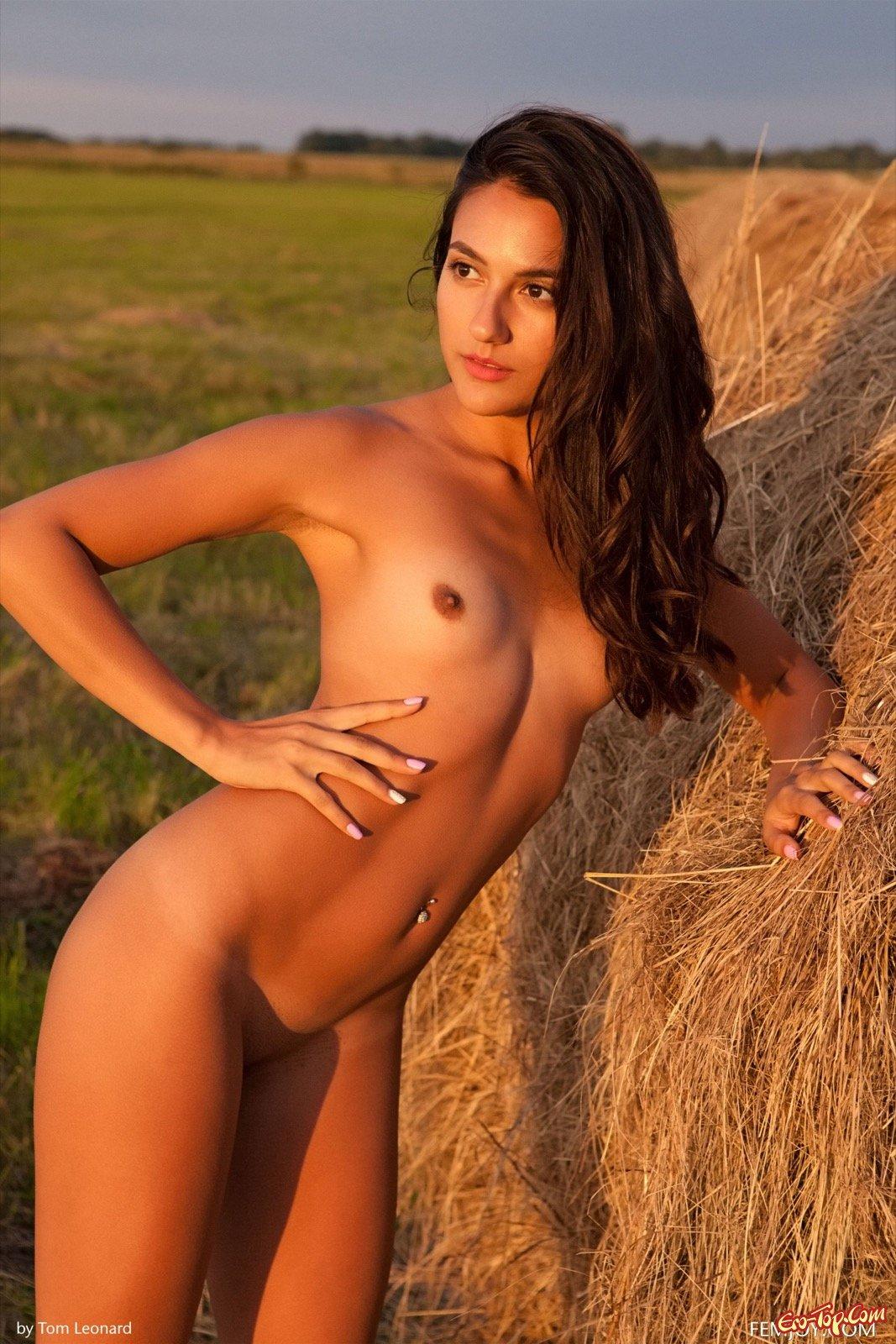 Нагая шатенка с пирсингом в пупке позирует в поле
