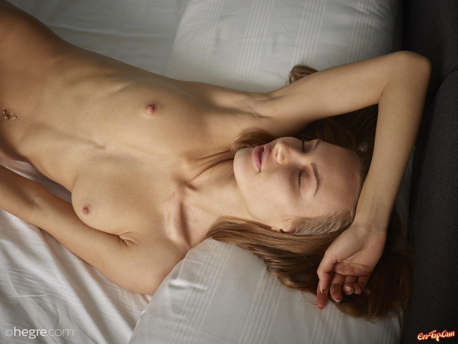 Раздетая девка с бритой киской нежится на кровати