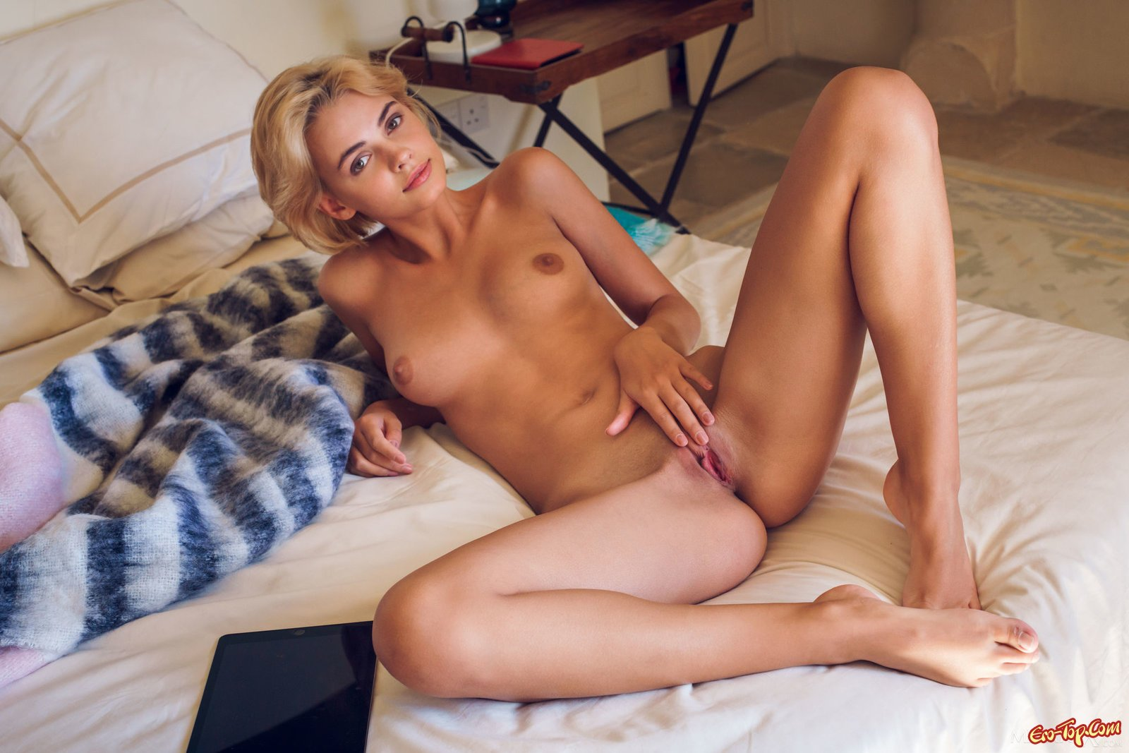 Милашка с выбритой киской теребит дырку пальчиком секс фото