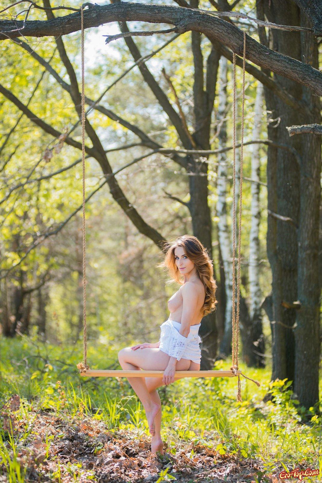Худенькая девушка в платье оголяется на природе