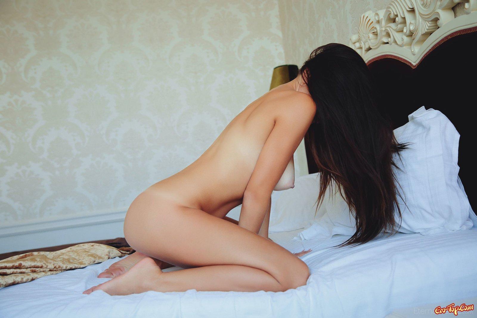 Обнаженная девушка с гладкой кожей лежит на кровати