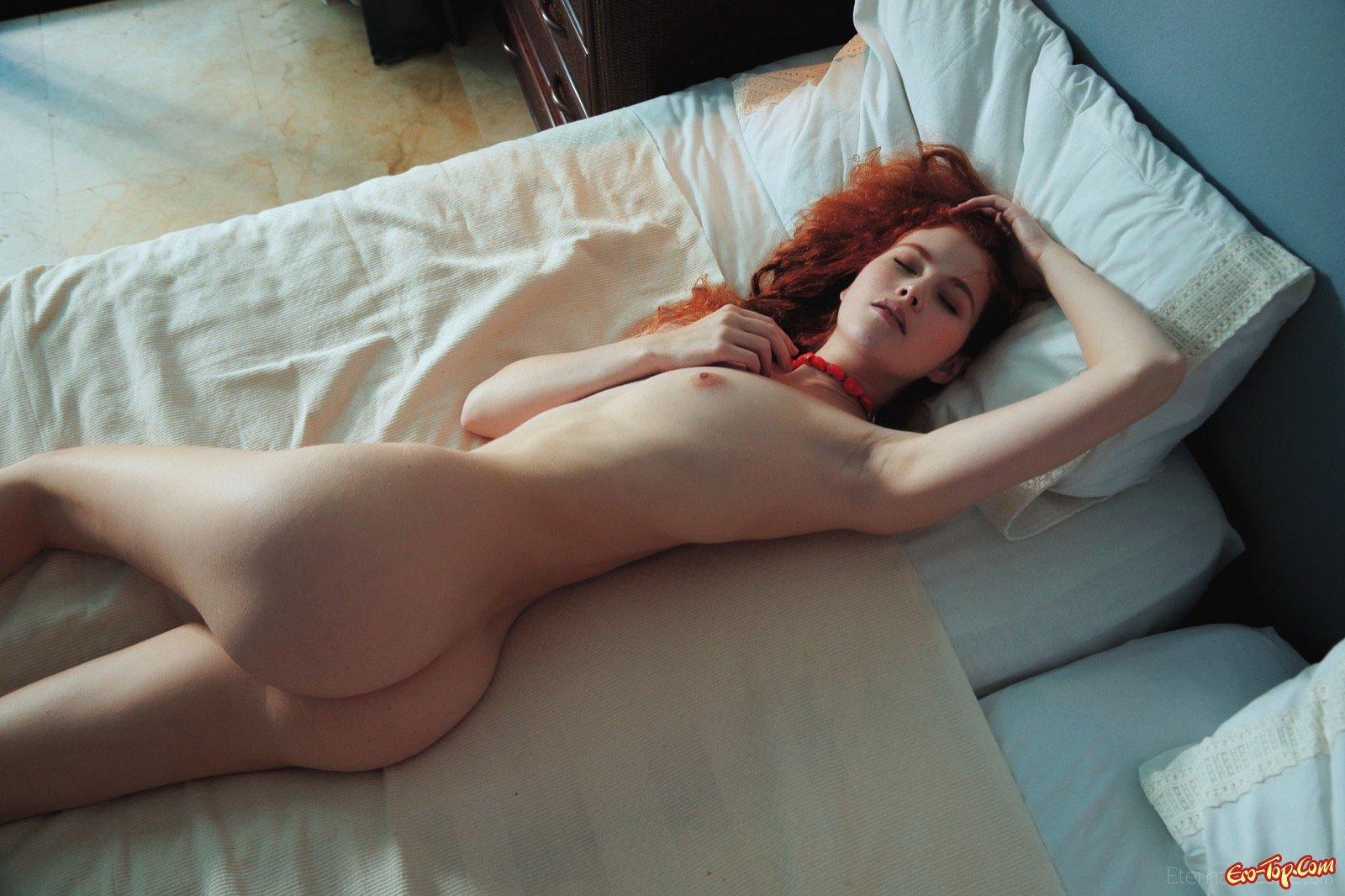 Рыженькая кудрявая блядь нагая лежит в кровати