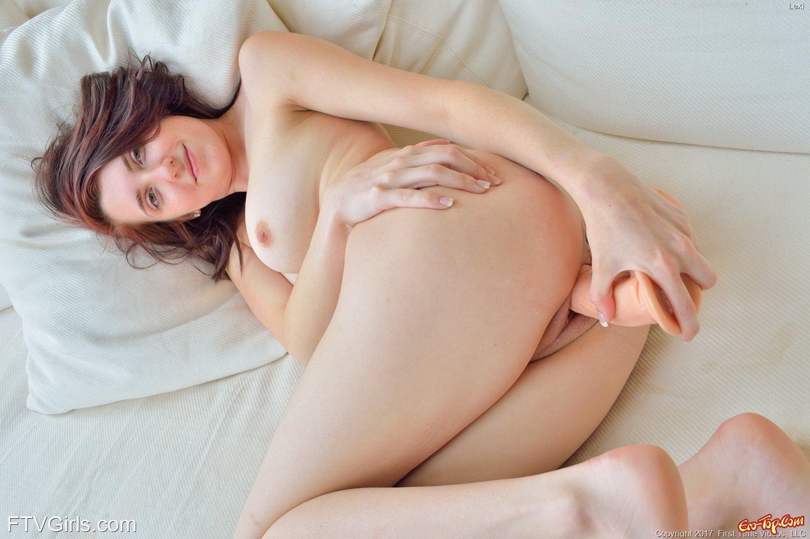 Голая девушка в постели с большим дилдо