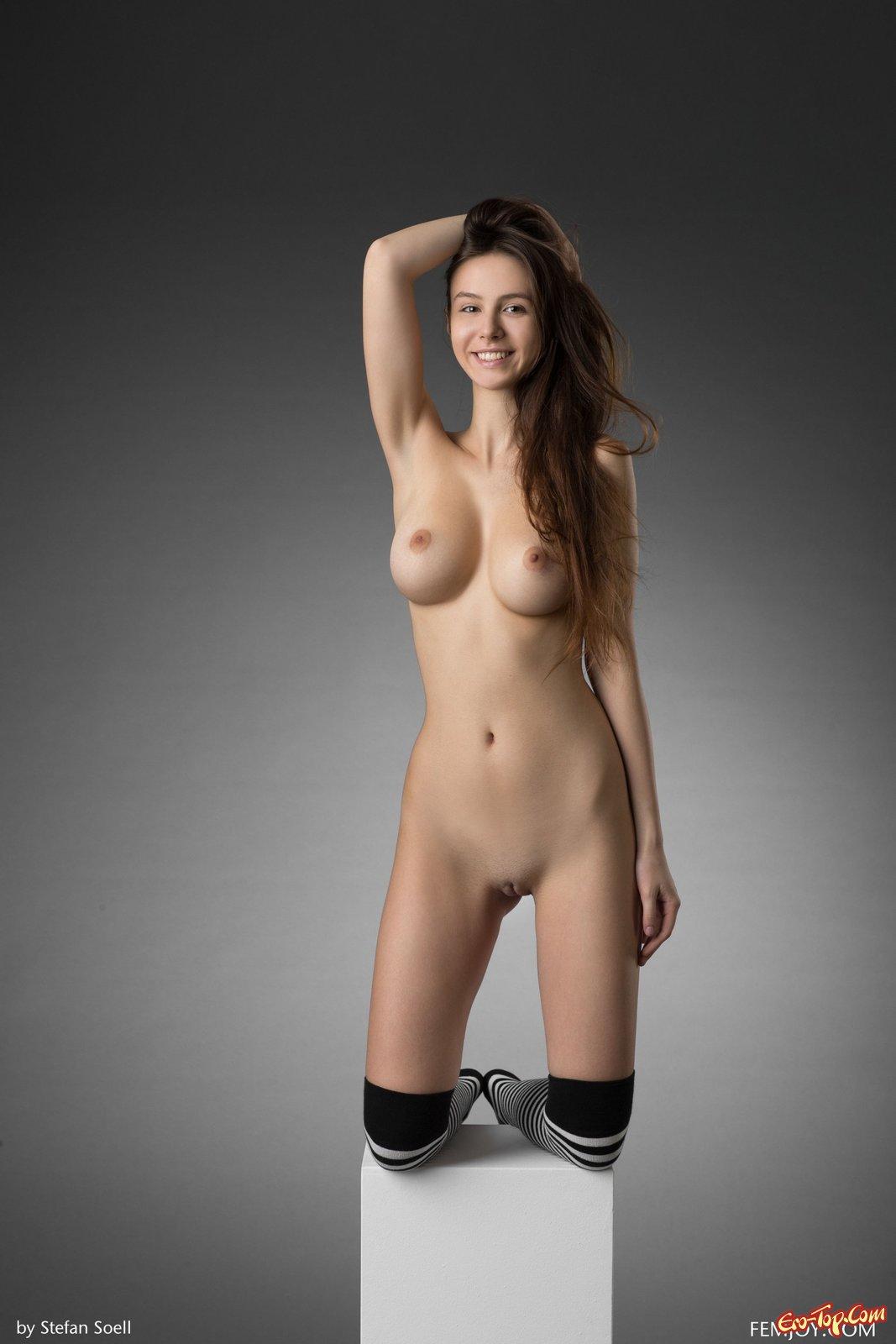 Голая красотка с шикарной грудью в полосатых чулках