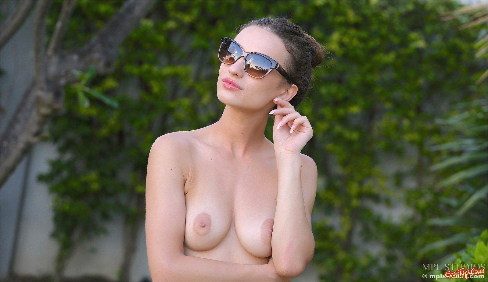 Привлекательная голая мадам на лавочке на поляне