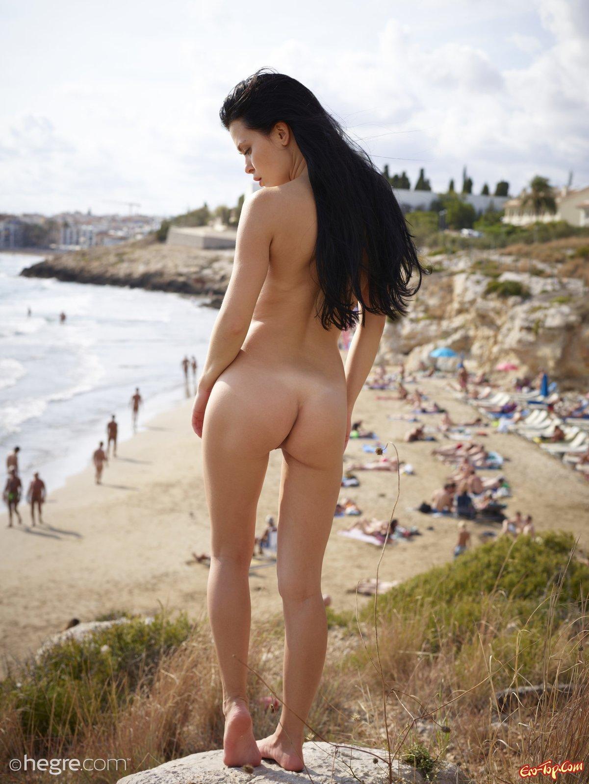 Обнаженная худая брюнетка на фоне нудистского пляжа