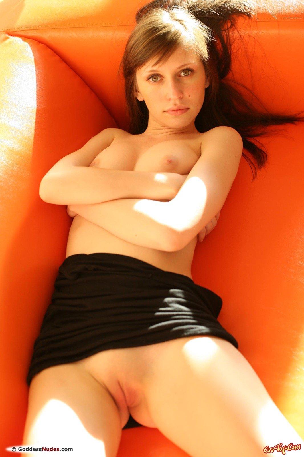 Девушка в платье без трусиков позирует на диване