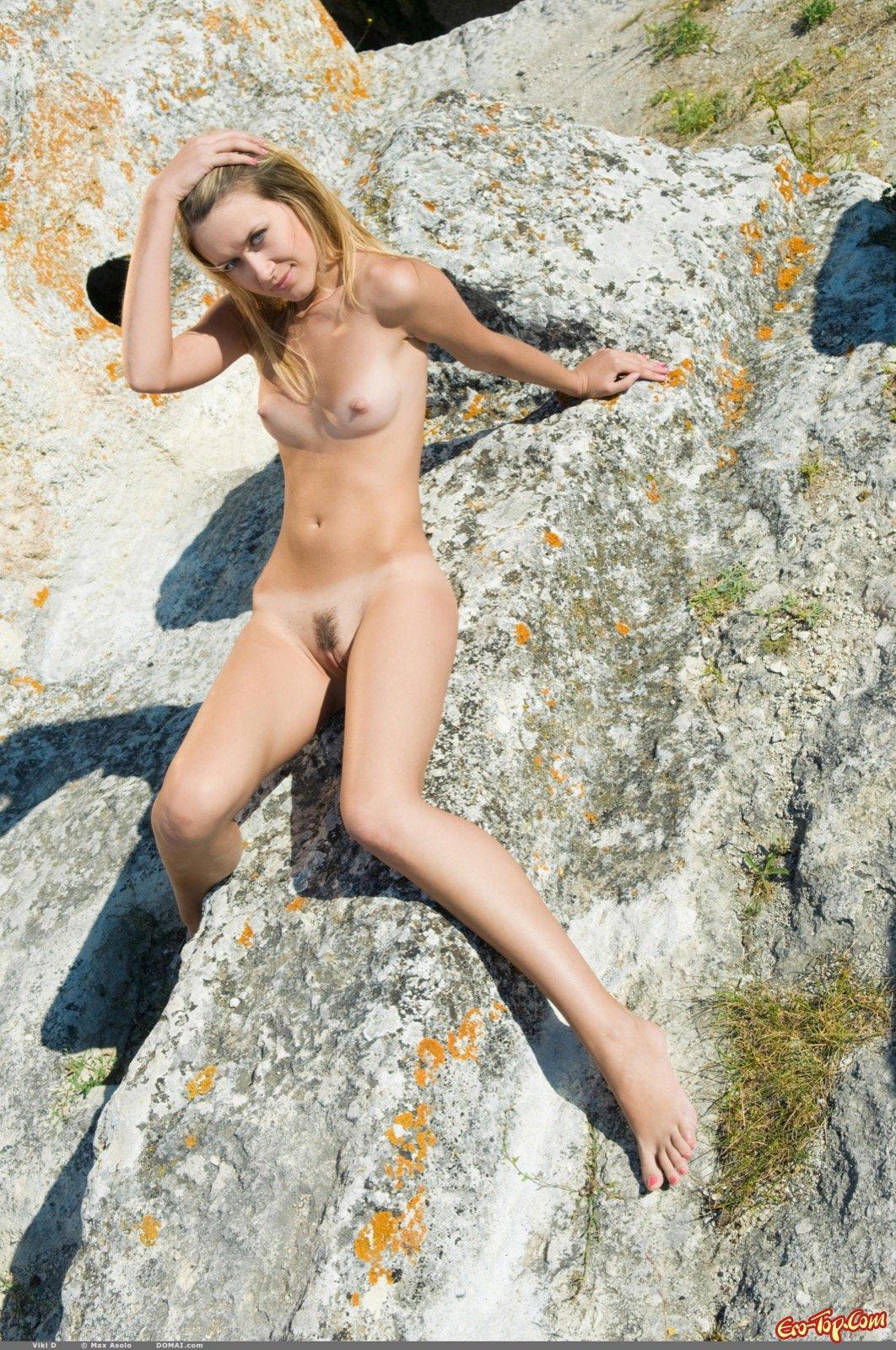 Совершеннолетняя худощавая девушка сексуально оголилась на скалах