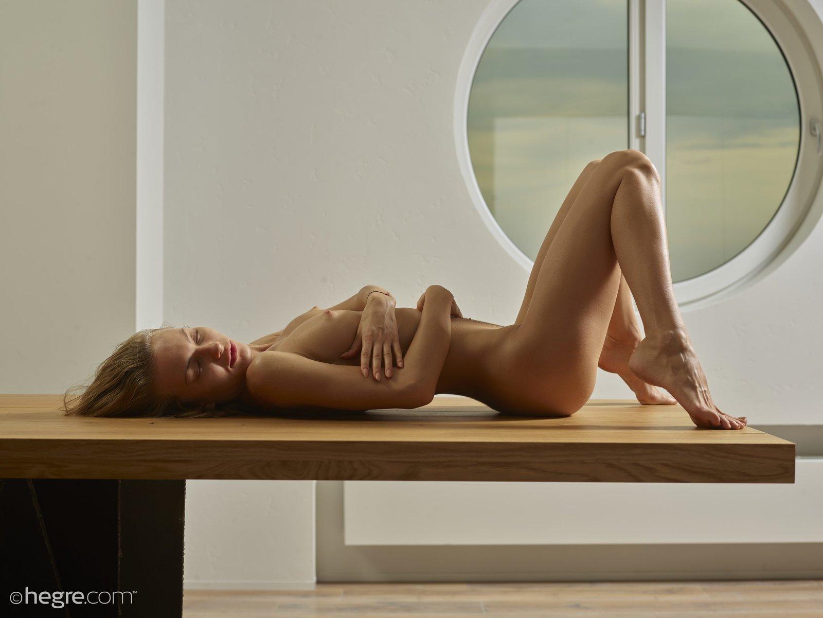 Обнаженная леди со красивой фигуркой фотографируется на столе