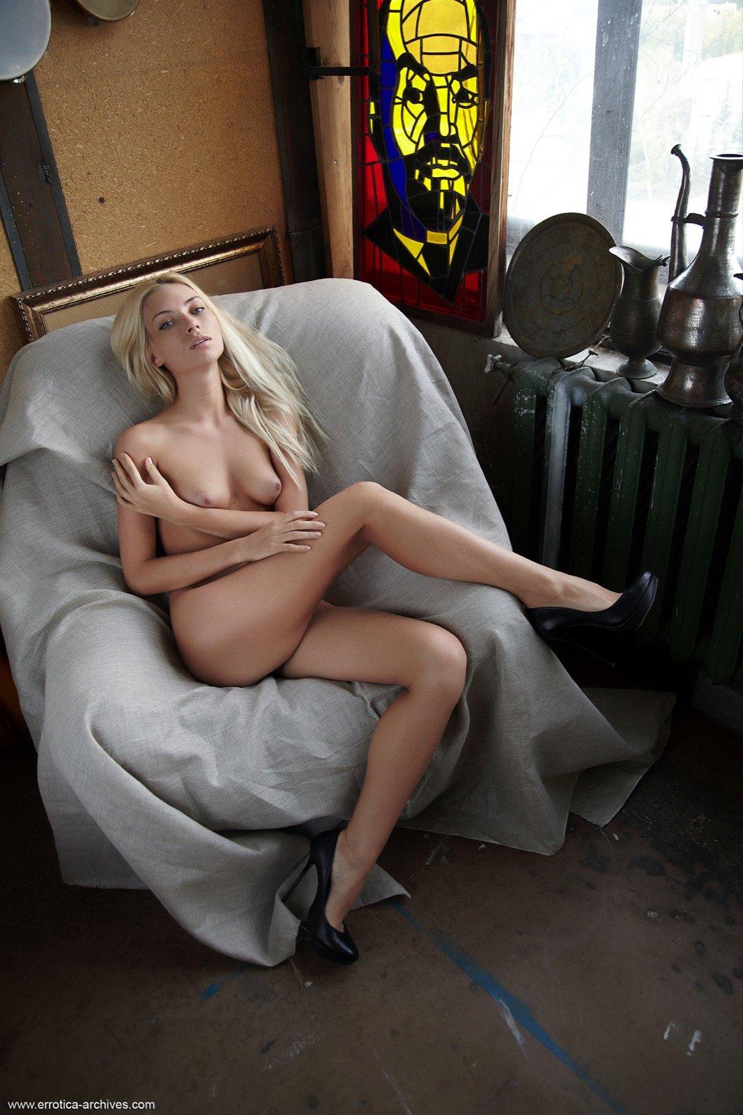 Голая блондиночка в туфлях раздвигает ножки в кресле