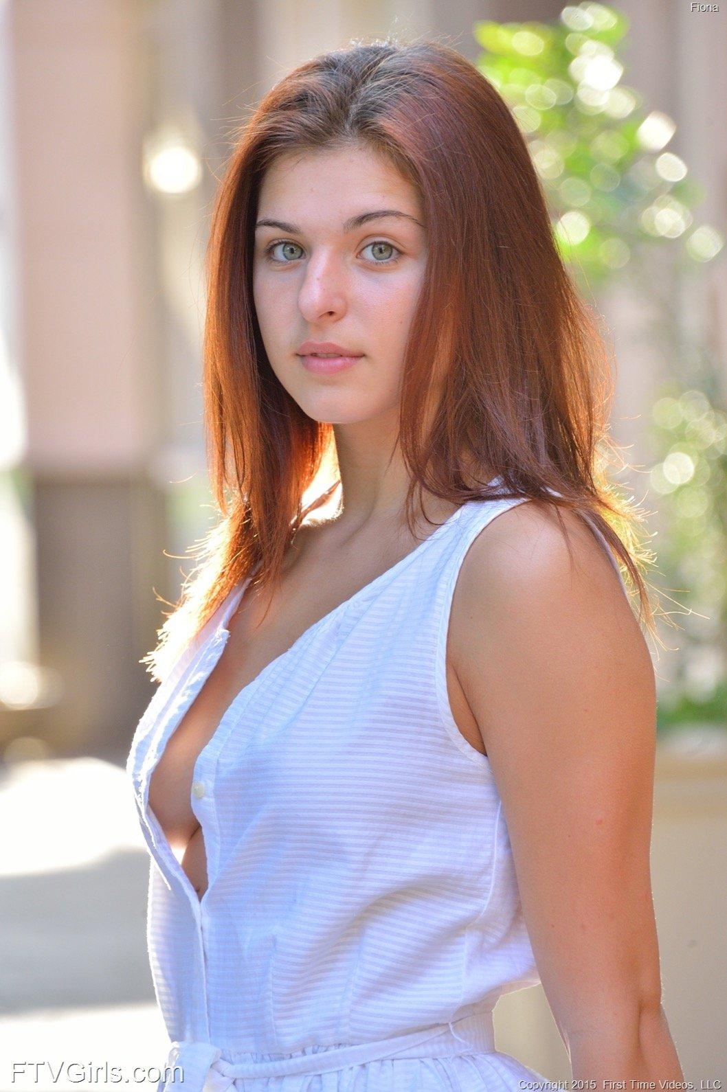 Молодая красотка в платье прогуливается по улице