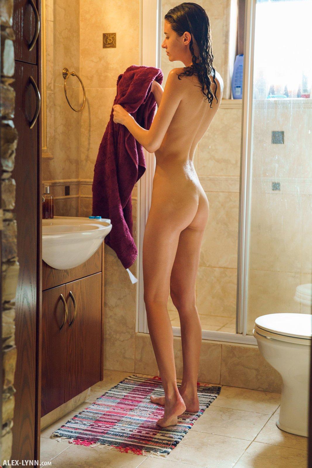 Голая девушка вытирается полотенцем после душа