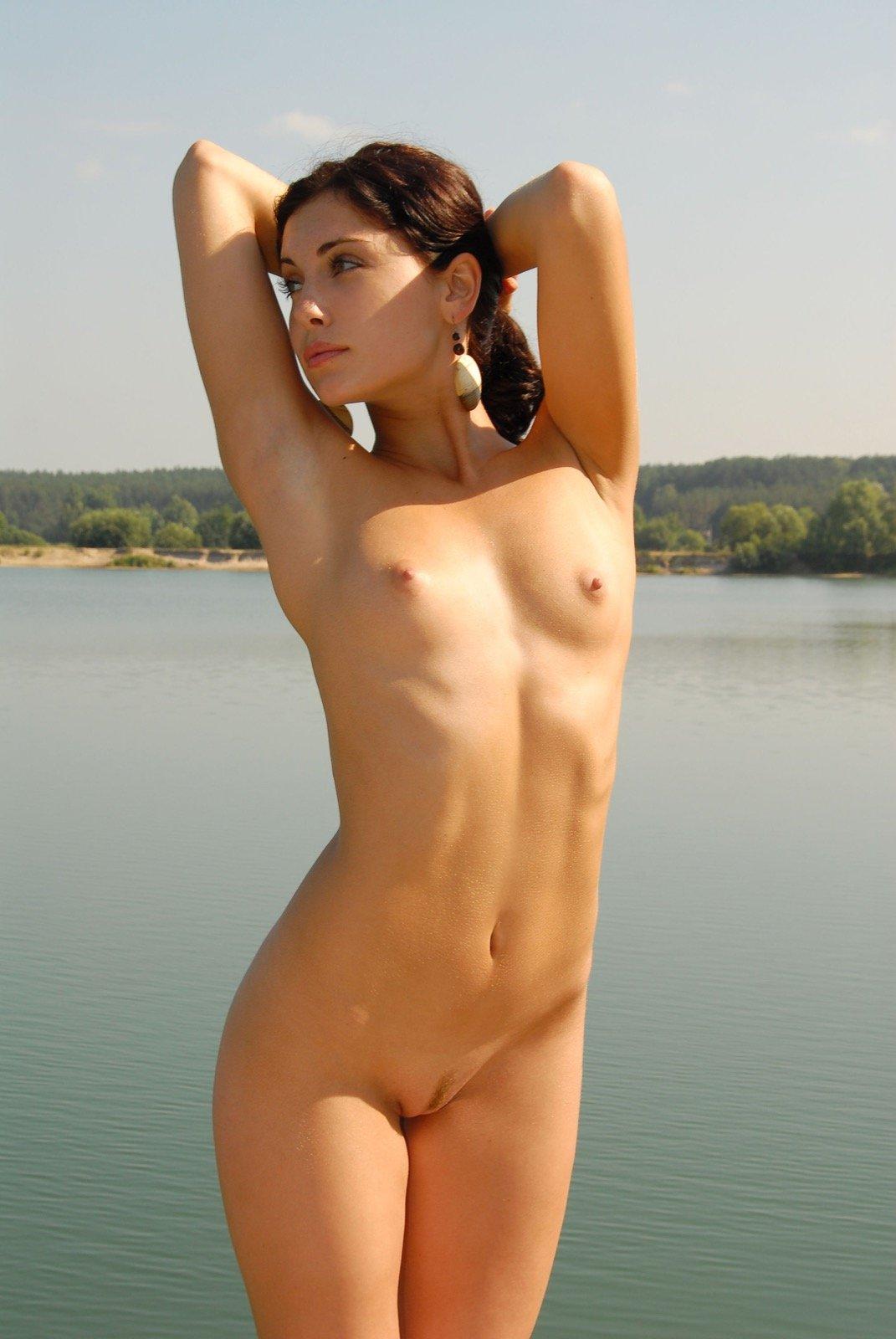 Голая девица с плоскими сиськами лежит на шезлонге