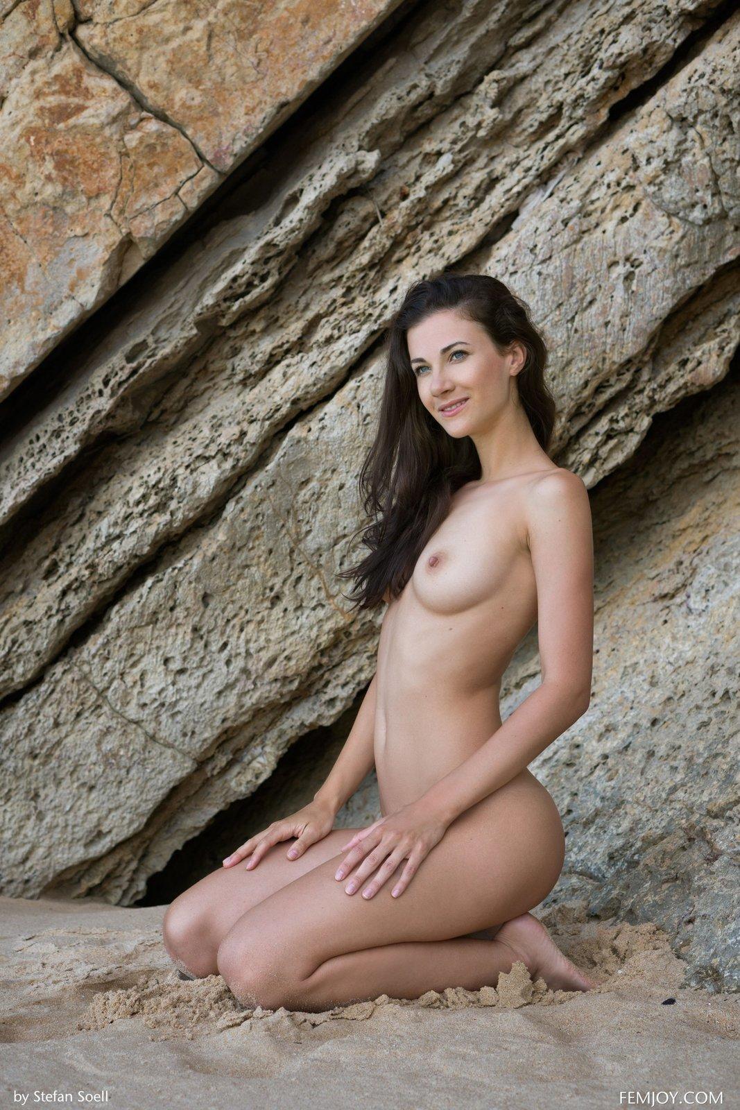 Красивая голая модель показала тело на фоне скал