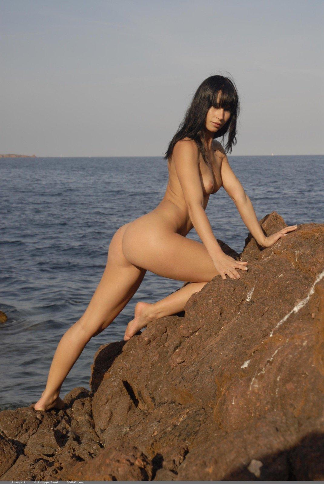Раздетая сексуальная красотка на камнях у моря