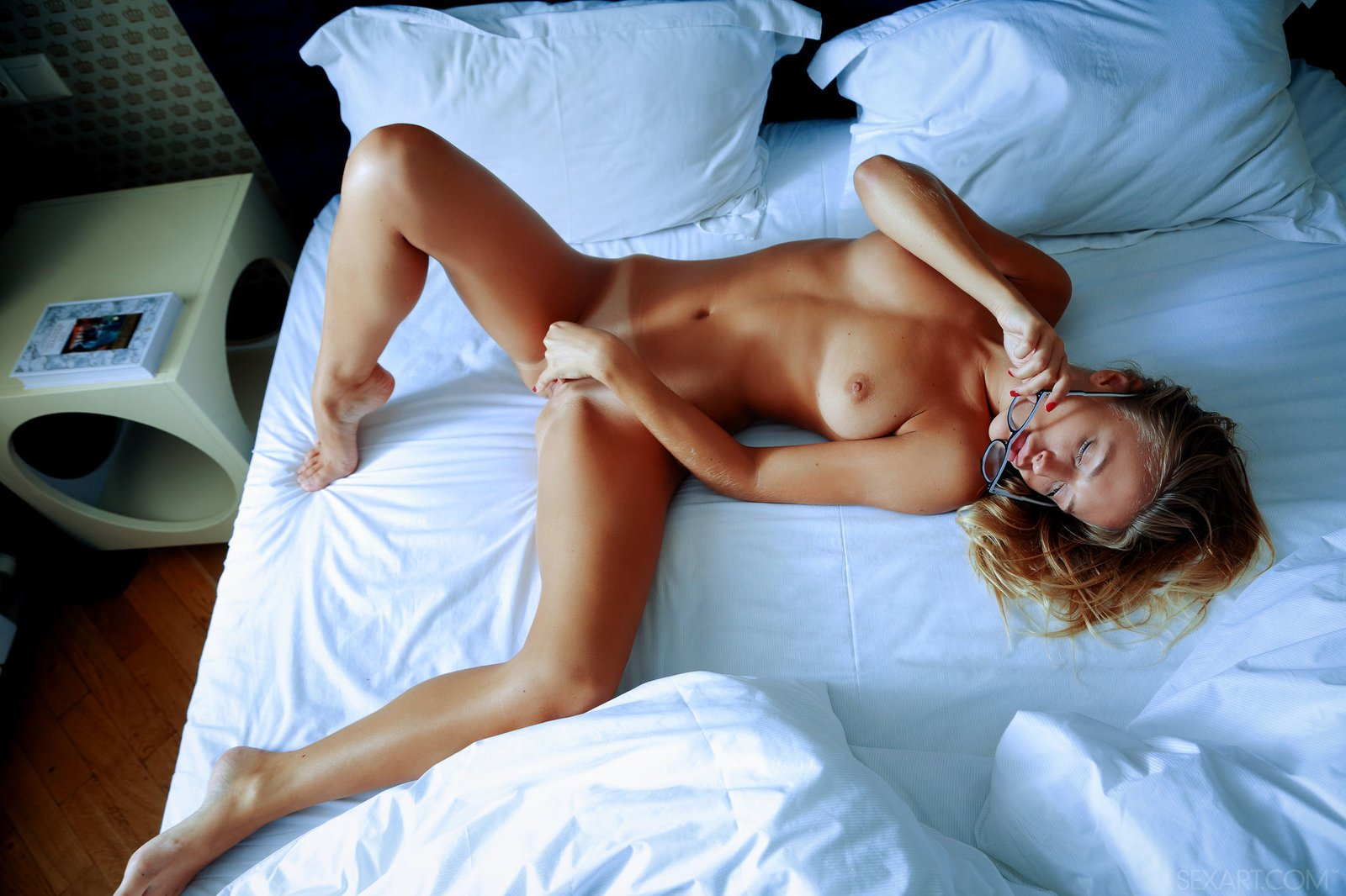 Голая чертовка в очках позирует на кровати
