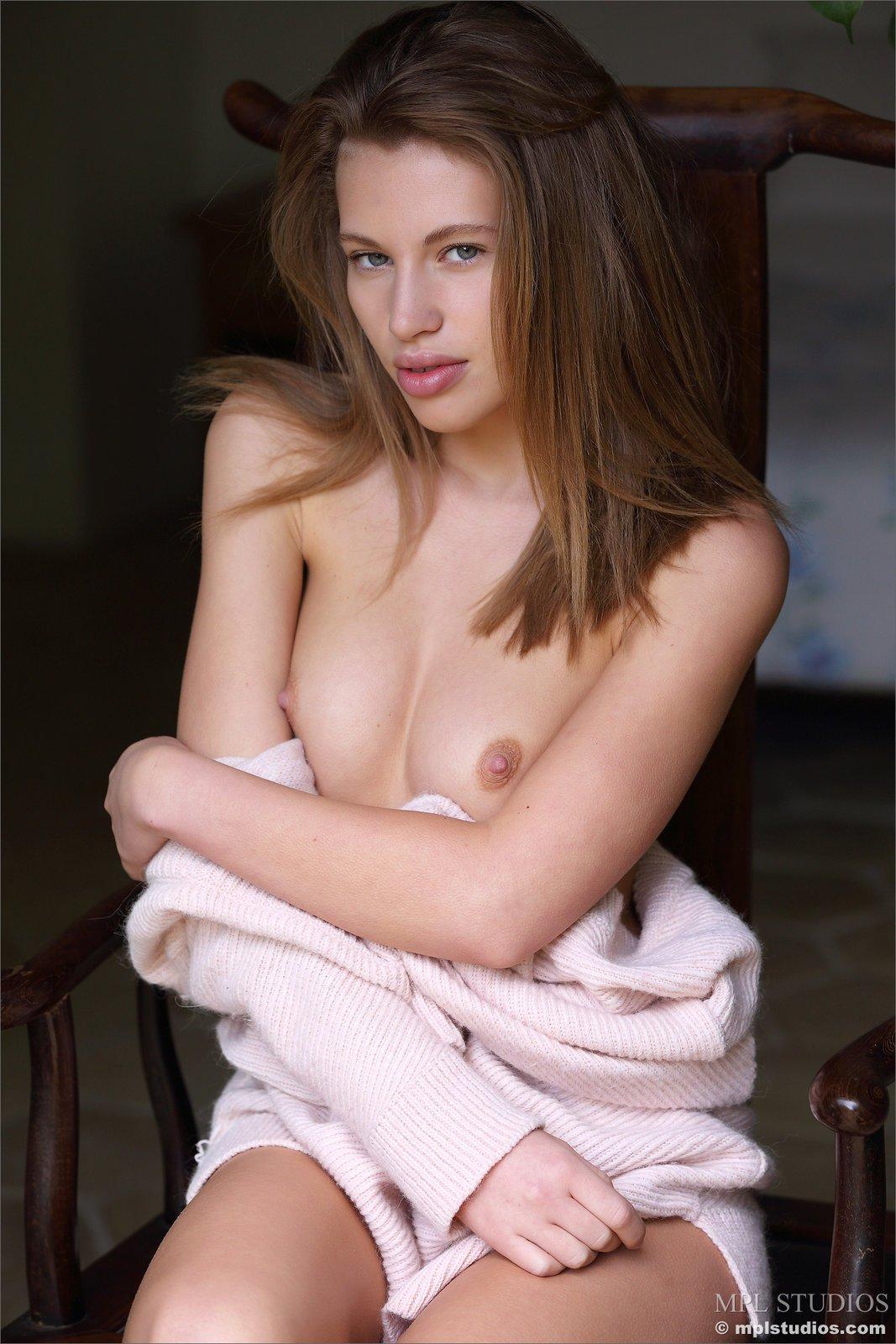 Девка пухлыми губками позирует голая на стульчике