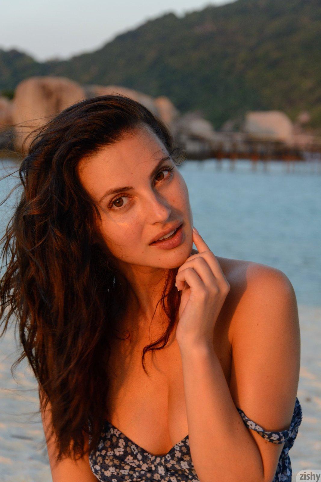 Эротичная девушка в купальнике расслабляется на берегу моря
