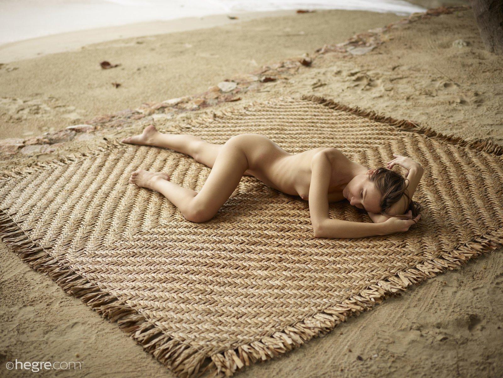 Голая тощая баба позирует на песке