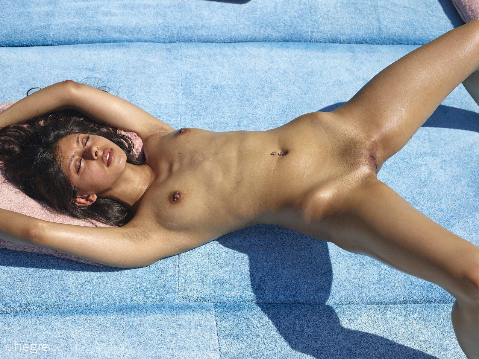 Ухоженная загорелая брюнеточка загарает раздетой секс фото